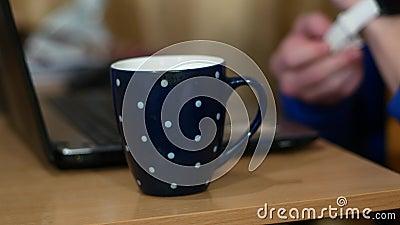 Freelancer работает над ноутбуком Около чашки с горячим напитком Мужчина пьет чай и снимает смарт-часы сток-видео