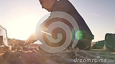 freelancer Силуэт человека работая на фрилансере компьтер-книжки сидя на солнце слепимости солнца захода солнца песка видеоматериал