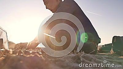 freelancer Силуэт человека работая на фрилансере компьтер-книжки сидя на солнце слепимости солнца захода солнца песка сток-видео