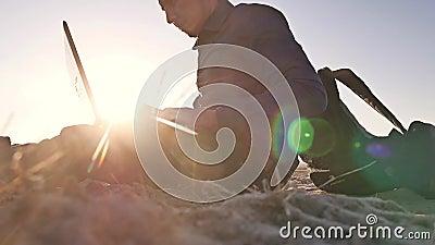 freelancer Человек работая на фрилансере компьтер-книжки сидя на силуэте солнца слепимости солнца захода солнца песка видеоматериал