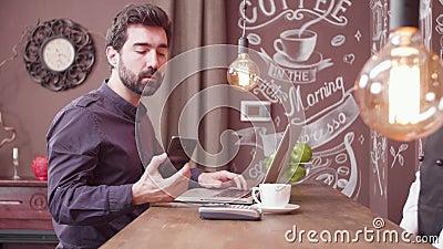 Freelancer novo que usa seu smartphone para fazer um pagamento em um contador da barra filme