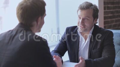 Freelancers having a conversation in front of a window sitting at the restaurant. Two businessmen or freelancers in a business clothes having a conversation stock footage
