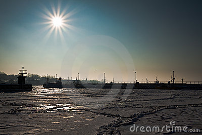 Freezed dock with boats at sunrise