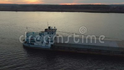 Freight ship floating on sea on sunset landscape. Aerial side view cargo ship with freight sailing in river on forest and sunset l. Andscape. Drone view from stock video footage