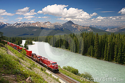 Freight train moving along Bow river in Canadian R