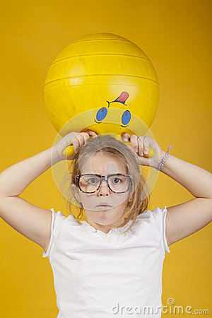 Freighten look of a young girl with a yellow ball