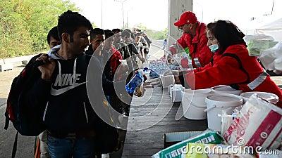 Freiwillige von verteilender Hilfe des roten Kreuzes für Flüchtlinge in Ungarn