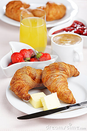 French breakfast with croissant, coffee, strawberry, and juice.