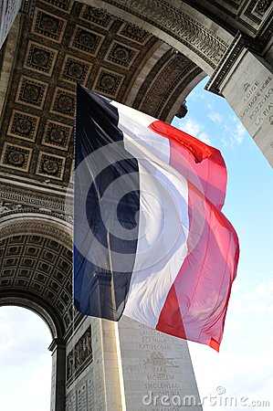French flag flying under Arc de Triomphe