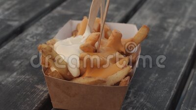 French fries fast food. French fries unhealthy fast food being taking and eaten from a card plate with mayonnaise by people stock footage