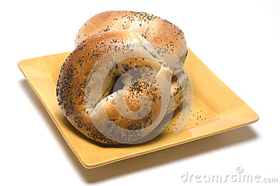 Fresh baked poppy seed bagels on plate