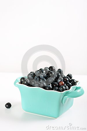 Fresh blueberries in blue bowl vertical