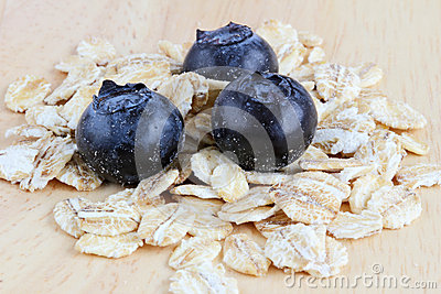 Fresh blueberries with oats on a wooden background