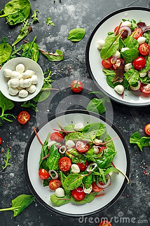 Free Fresh Cherry Tomato, Mozzarella Salad With Green Lettuce Mix And Red Onion. Served On Plate. Healthy Food. Royalty Free Stock Photography - 115505907