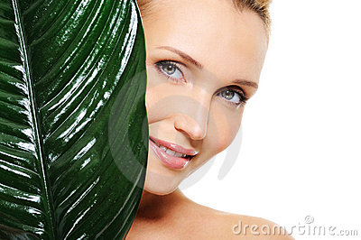 Fresh clear face of young woman behind the plant