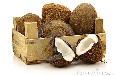 Fresh coconuts and a cut one in a wooden crate