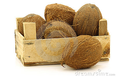 Fresh coconuts in a wooden crate
