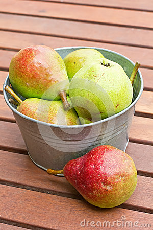 Fresh colourful pears in bowl on wooden backgro