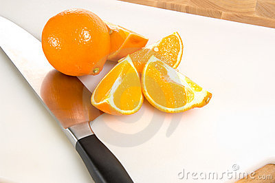 Fresh cut oranges on cutting board with knife