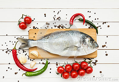 Fresh dorado fish on wooden cutting board with vegetables on white wooden table. Top view Stock Photo
