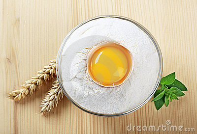 Fresh egg in a bowl of flour