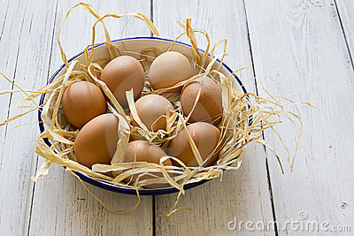 Fresh eggs in enamel bowl on wood background