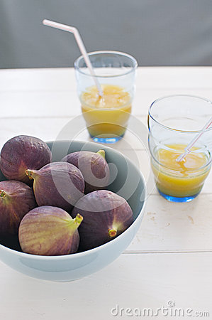 Fresh figs in turquoise bowl with orange juice