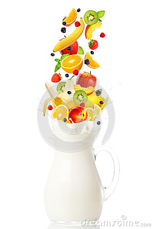 Fresh fruits falling into the jar with milk