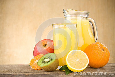 Fresh fruits juice in glass and slices on wood