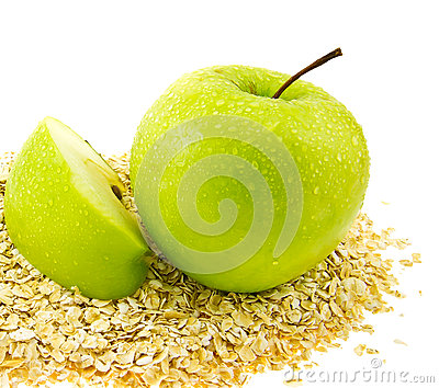 Fresh green apple with a segment on oat flakes.