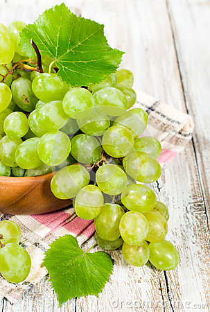 Fresh green grapes in a wooden bowl