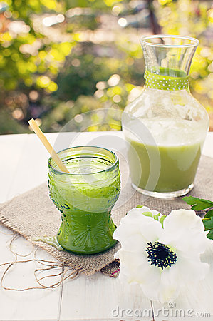 Fresh green juice on rustic table with white flowe