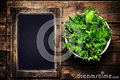 Fresh green Lettuce Salad on blank vintage slate chalk board on