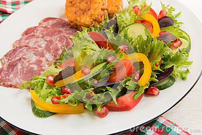 Fresh mixed vegetable salad and sliced sausage