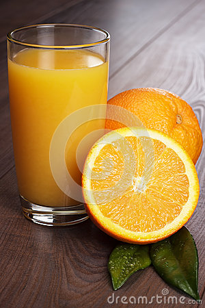 Fresh orange and glass with juice on the table