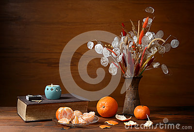 Fresh oranges and dried flowers in a vase