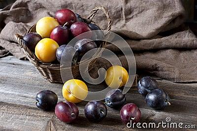 Fresh plums in basket on wooden board
