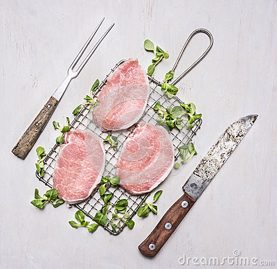 Free Fresh Raw Pork Steaks With Herbs, A Knife And Fork For The Meat On The Grill For Roasting Wooden Rustic Background Top View Royalty Free Stock Images - 68689159