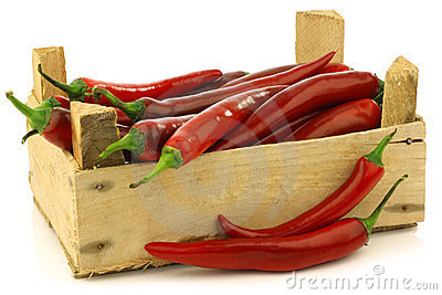 Fresh red chili peppers in a wooden crate