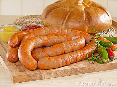 Fresh sausage on a cutting board with bread