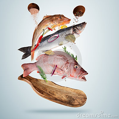 Free Fresh Sea Fish With Falling Spices, Flying Above Wooden Board Stock Image - 92920641