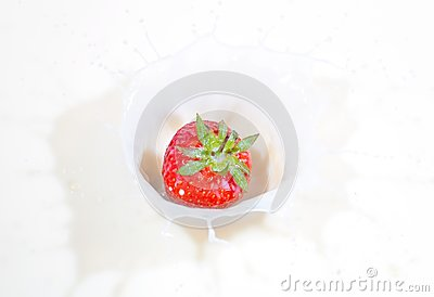 Fresh strawberry splashing into milk