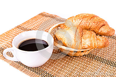 Fresh and tasty French croissants in a basket and cup of coffee served