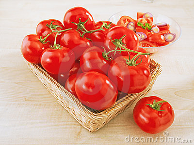 Fresh tomatoes in a wicker basket on table