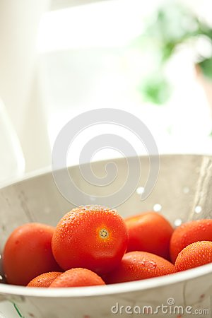 Fresh, Vibrant Roma Tomatoes in Colander with Wate