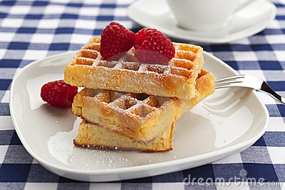 Fresh waffles with powdered sugar and raspberries