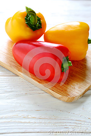 Fresh yellow and red peppers on a chopping board