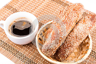 Freshly baked bread rolls with sesame with cup of coffee