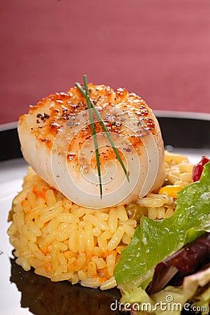 Freshly seared sea scallop on saffron rice