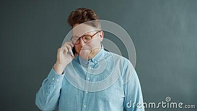 Freuer Typ, der über das Handy lacht und die Kommunikation auf grauem Hintergrund genießt stock video footage